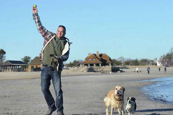 Greenwich resident Chance Patterson plays fetch with his dogs, Buckeye, a Labrador Retriever and Lulu, right, a mixed breed, during lowtide on the beach at Greenwich Point, Conn., Thursday, Jan. 25, 2018.