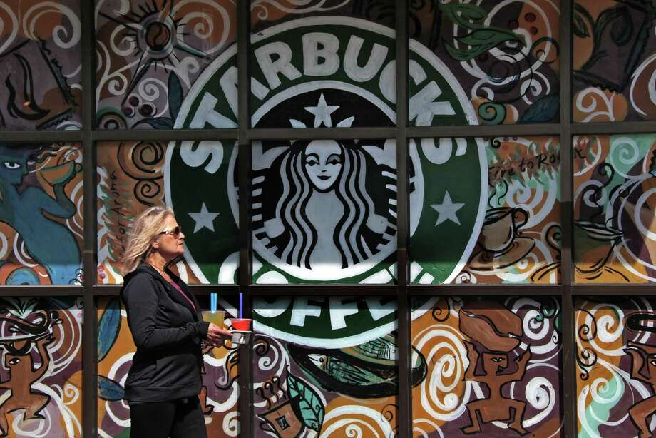 A woman walks past a Starbucks coffee shop in Sewickley, Pa. Starbucks global same-store sales rose 2 percent last quarter, missing the 3 percent average of analysts' estimates, according to Consensus Metrix. Photo: File Photo /Associated Press / Copyright 2017 The Associated Press. All rights reserved.
