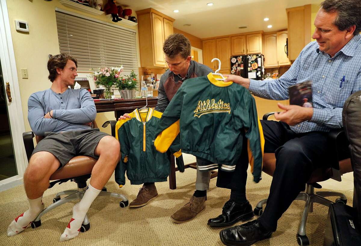 Mike Piscotty, right, displays the jackets that his two sons Austin, left, and Nick, center, wore in a family photo with their brother Stephen at their home in Pleasanton, Calif., on Monday, January 22, 2018. Stephen Piscotty, who was raised in the East Bay a die hard A's fan, was traded from the St. Louis Cardinals to the A's in the offseason. The move has brought him home an opportune time, as his mother Gretchen was recently diagnosed with ALS.