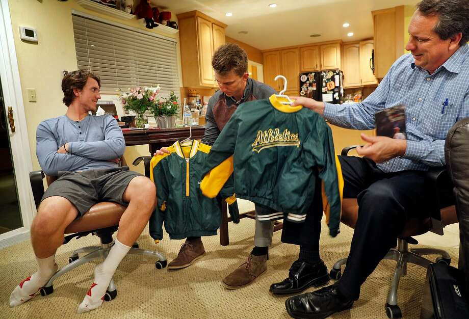 Mike Piscotty, right, displays the jackets his two sons Austin, left, and Nick, center, wore in a family photo with their brother, Stephen. Photo: Carlos Avila Gonzalez, The Chronicle