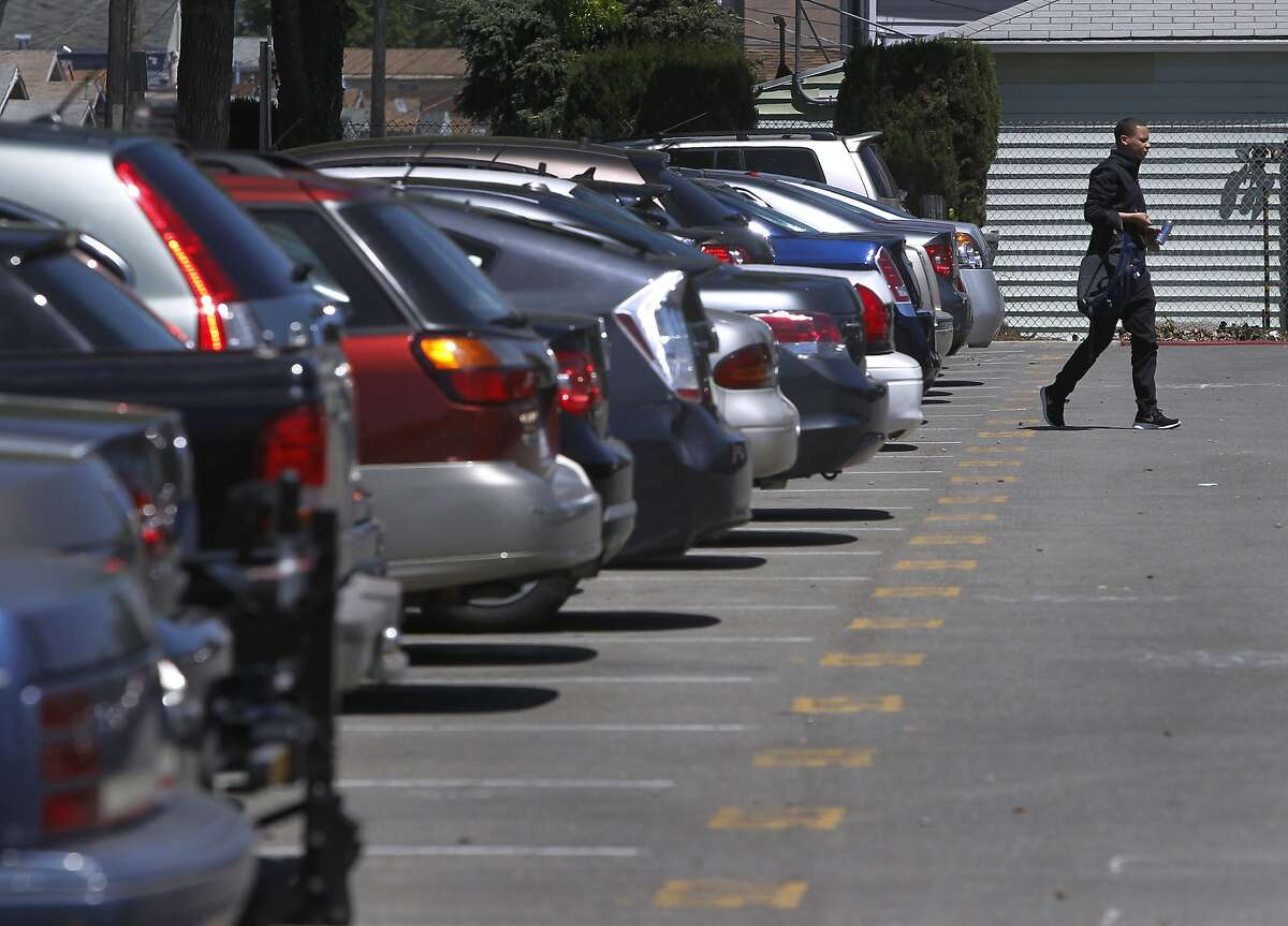 FILE-- A commuter walks to the Coliseum station after finding a space in a BART parking lot in Oakland on Thursday, April 30, 2015. BART officials are looking at overhauling their parking policies to allow prices that increase or decrease depending on demand and using license-plate readers to determine who's paid for a space and who gets a citation.