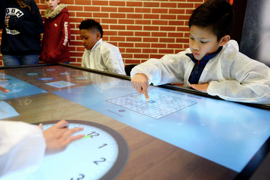 Rylan Phan, a Charlton-Pollard Elementary fourth grader, plays on a touchscreen table at an open house for Beaumont ISD's new STEM Center at the former Austin Middle School on Thursday afternoon. The center will serve as a lab for students from the district to learn about science, technology, engineering and math fields.  Photo taken Thursday 1/25/18 Ryan Pelham/The Enterprise Photo: Ryan Pelham / ©2017 The Beaumont Enterprise/Ryan Pelham