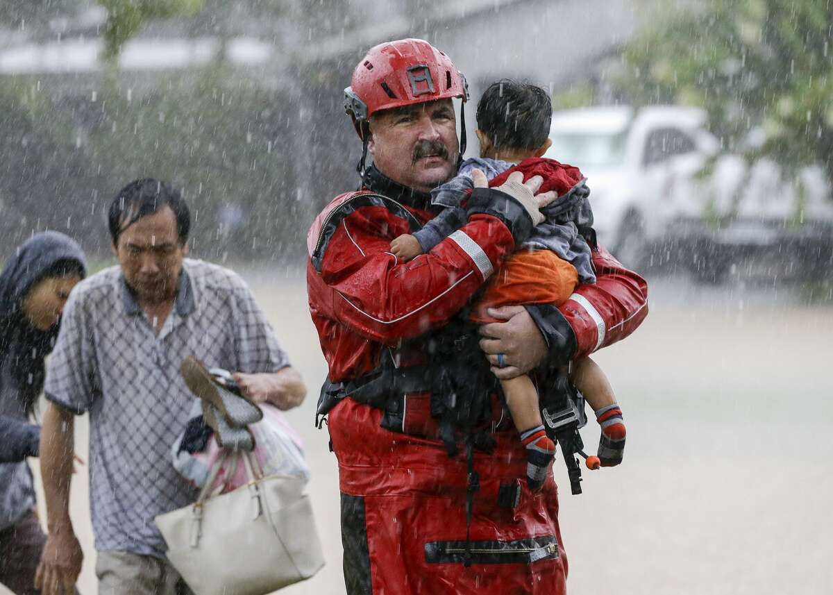 Chad Smith, a Task Force One member from the Dallas Fire Dept., carries Christian Rodriguez, 1, from a rescue boat as people are transferred to a pickup point in Houston during the aftermath of Hurricane Harvey on Sunday, Aug. 27, 2017.