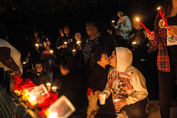 Ruby Rodriguez kisses her son, Noah, while lighting candles during a vigil for Angel Ramos, a 21-year-old man who was shot and killed by Vallejo Police, marking the one year anniversary of his death Tuesday, Jan. 23, 2018 in Vallejo, Calif.
