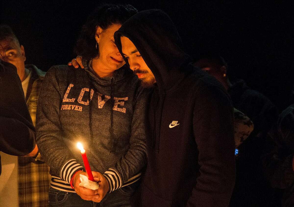 Dante Ramos holds his mother, Annice Evans, as she cries during a candlelight vigil for her son, Angel Ramos, who was shot and killed by Vallejo Police, on the one year anniversary of his death Tuesday, Jan. 23, 2018 in Vallejo, Calif.