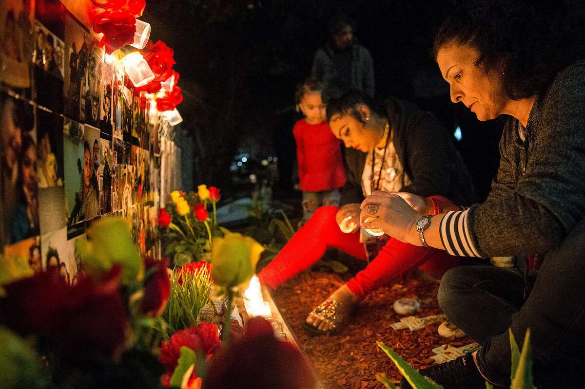 Alicia Saddler, center, and Annice Evans light candles for a vigil in front of their house remembering their brother and son Angel Ramos, who was shot and killed by Vallejo Police, Tuesday, Jan. 23, 2018 in Vallejo, Calif.