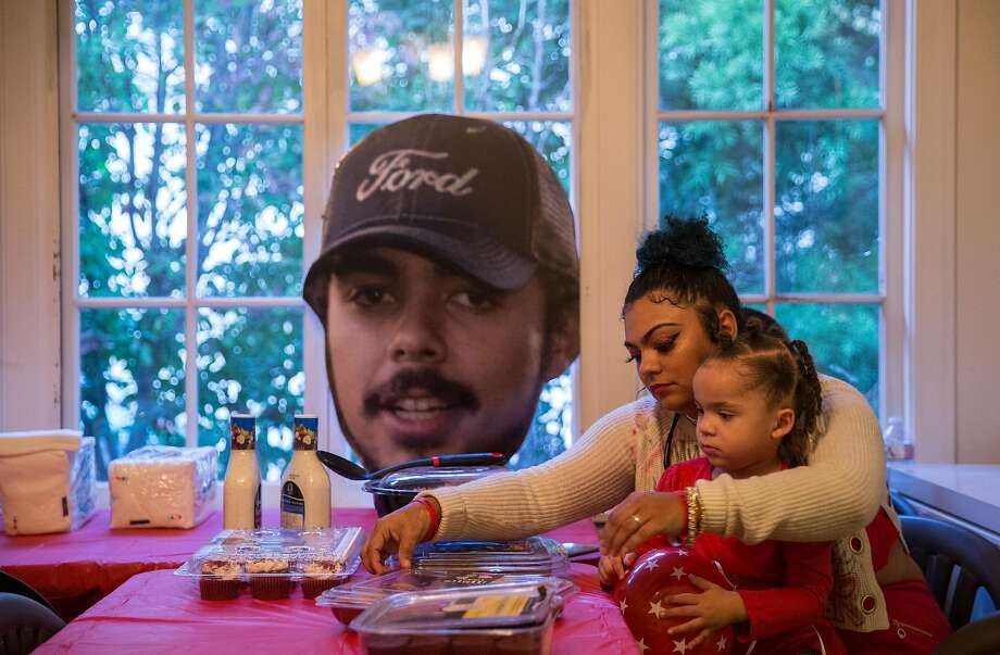 Alicia Saddler, sister of Angel Ramos who was shot and killed by Vallejo Police, holds her daughter, Khloe, 3, while sitting near a cut-out of Angel's face in their family dining room Tuesday, Jan. 23, 2018 in Vallejo, Calif. Photo: Jessica Christian, The Chronicle