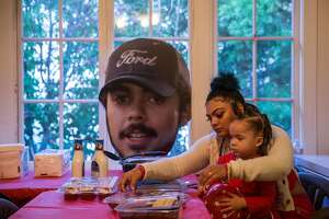 Alicia Saddler, sister of Angel Ramos who was shot and killed by Vallejo Police, holds her daughter, Khloe, 3, while sitting near a cut-out of Angel's face in their family dining room Tuesday, Jan. 23, 2018 in Vallejo, Calif.