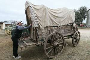 "Joanie Sellars Edwards, owner of The Nest Estate Sale Services, inspects a chuckwagon listed for $9,900 at the Alamo Village near Brackettville on Jan. 25, 2018. About 2,400 items will be sold this weekend from the movie set, where 72 motion pictures were filmed since the early 1950s, including ""The Alamo"" in 1959."