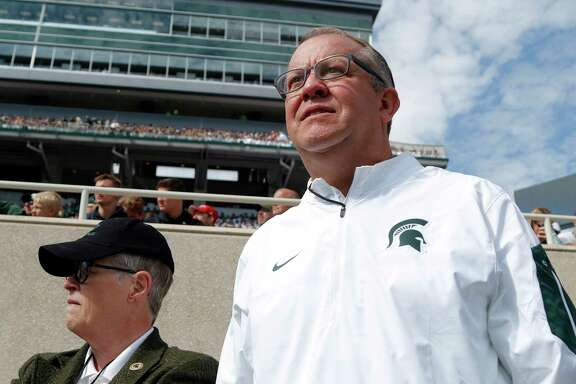 Michigan State athletic director Mark Hollis, right, could be in jeopardy as a result of the Larry Nassar abuse scandal. President Lou Anna Simon resigned Wednesday.