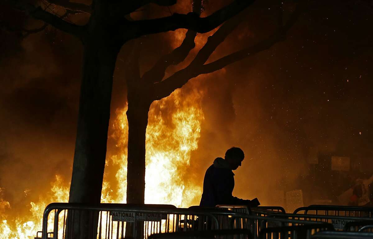 FILE - In this Wednesday, Feb. 1, 2017, file photo, a bonfire set by demonstrators protesting a scheduled speaking appearance by Breitbart News editor Milo Yiannopoulos, burns on Sproul Plaza on the University of California at Berkeley campus on in Berkeley, Calif. Four people who say they were injured last year during a riot ahead of a speech by right-wing provocateur Milo Yiannopoulos at the University of California, Berkeley have filed a lawsuit against the university and the city of Berkeley. (AP Photo/Ben Margot, File)