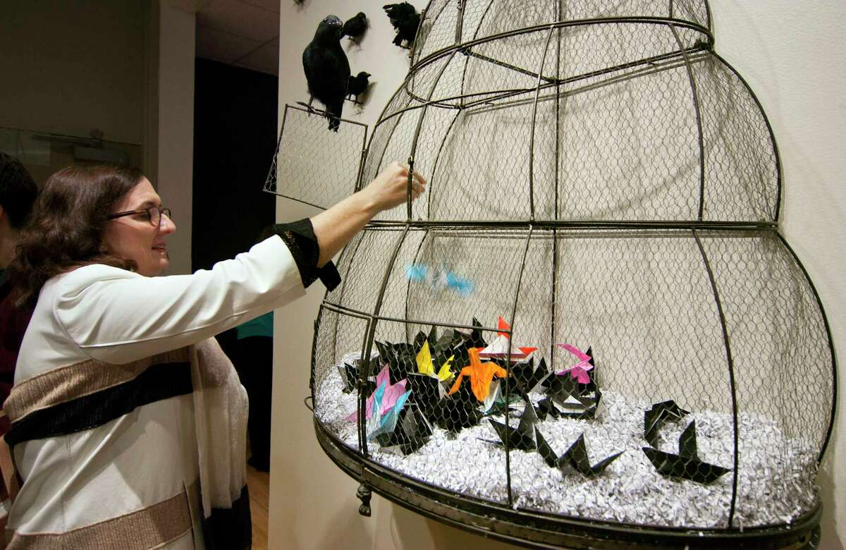 Ellen Greenberg, of Westport, drops a bird she created as part of the opening reception exhibit entitled