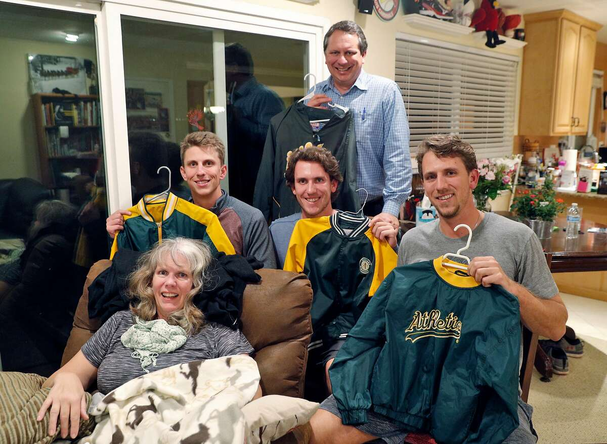 Stephen Piscotty, right, with his brothers Austin, center, and Nick, left, and dad, Mike holding their A's jackets with there mom Gretchen, their home in Pleasanton, Calif., on Monday, January 22, 2018. Piscotty, who was raised in the East Bay a die hard A's fan, was traded from the St. Louis Cardinals to the A's in the offseason, and announced his return with a family photo wearing the jackets they're holding. The move has brought him home an opportune time, as his mother Gretchen was recently diagnosed with ALS.