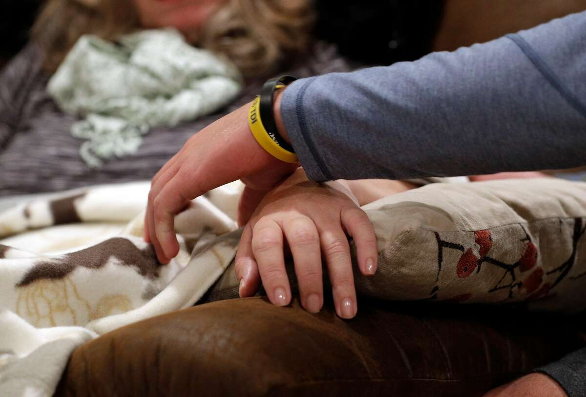 Austin Piscotty, Stephen Piscotty's youngest brother, adjusts his mother's hand on a pillow when she was uncomfortable while in their home in Pleasanton, Calif., on Monday, January 22, 2018. Stephen Piscotty, who was raised in the East Bay a die hard A's fan, was traded from the St. Louis Cardinals to the A's in the offseason. The move has brought him home an opportune time, as his mother Gretchen was recently diagnosed with ALS.