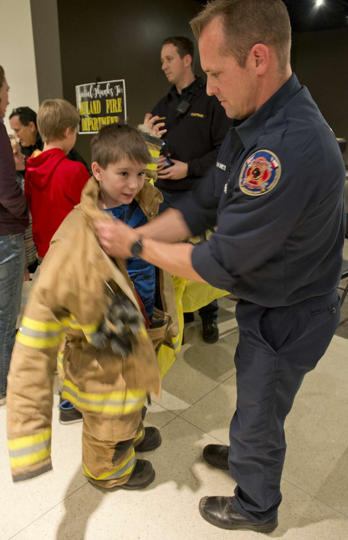 """Jackson Johnson tries on fire fighter gear with the help of MFD Engineer Shawn Van Meter 01/25/18 evening at the Petroleum Museum's Family Science Night, """"Forces of Nature."""" Tim Fischer/Reporter-Telegram"""