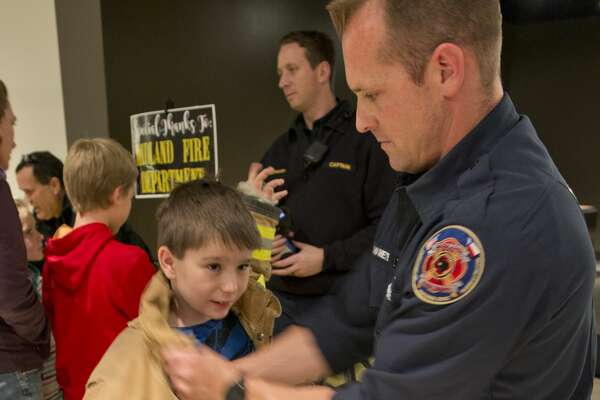 "Jackson Johnson tries on fire fighter gear with the help of MFD Engineer Shawn Van Meter 01/25/18 evening at the Petroleum Museum's Family Science Night, ""Forces of Nature."" Tim Fischer/Reporter-Telegram"