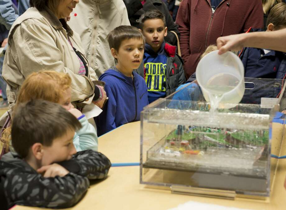 "Children watch a demonstration of heavy rain and runoff 01/25/18 evening at the Petroleum Museum's Family Science Night, ""Forces of Nature."" Tim Fischer/Reporter-Telegram Photo: Tim Fischer/Midland Reporter-Telegram"