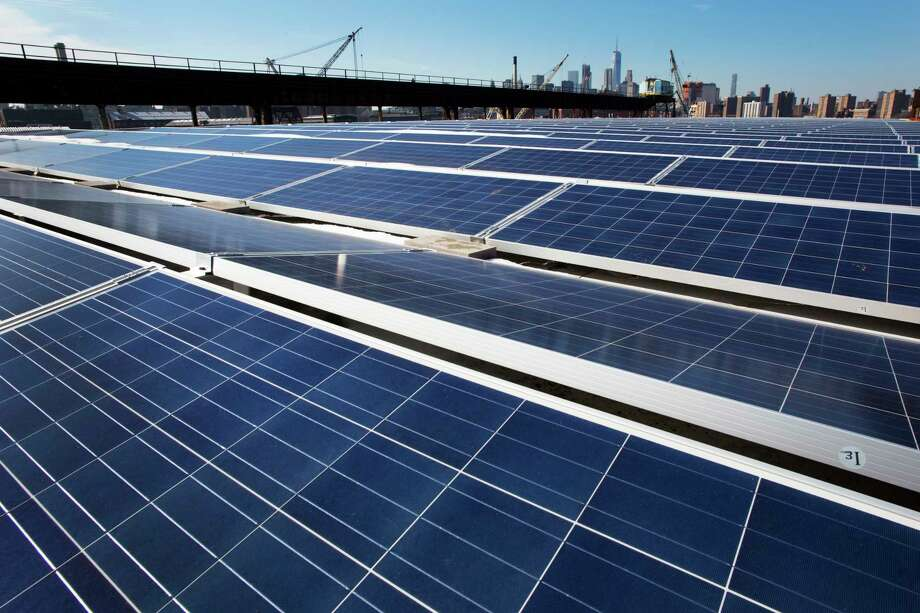 A rooftop is covered with solar panels at the Brooklyn Navy Yard, Tuesday, Feb. 14, 2017, in New York.  >>Animals threatened by climate change Photo: Mark Lennihan, STF / Copyright 2017 The Associated Press. All rights reserved.