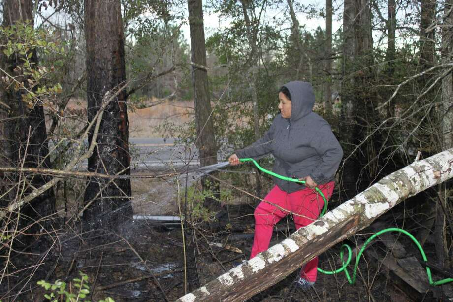 Anna Diaz uses a waterhose to douse a grass fire at her home on Plum Grove Road. The fire was one of several believed to have been set by an arsonist Thursday afternoon in the Cleveland area. Photo: Vanesa Brashier