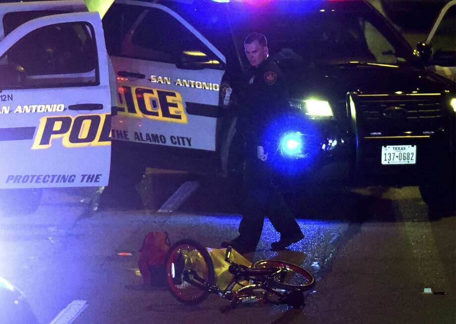A crumpled bicycle and a body lay on Loop 410 East at McCullough after a man was shot by police  on Thursday night, Jan. 25, 2018. Photo: Billy Calzada, Staff / San Antonio Express-News / San Antonio Express-News