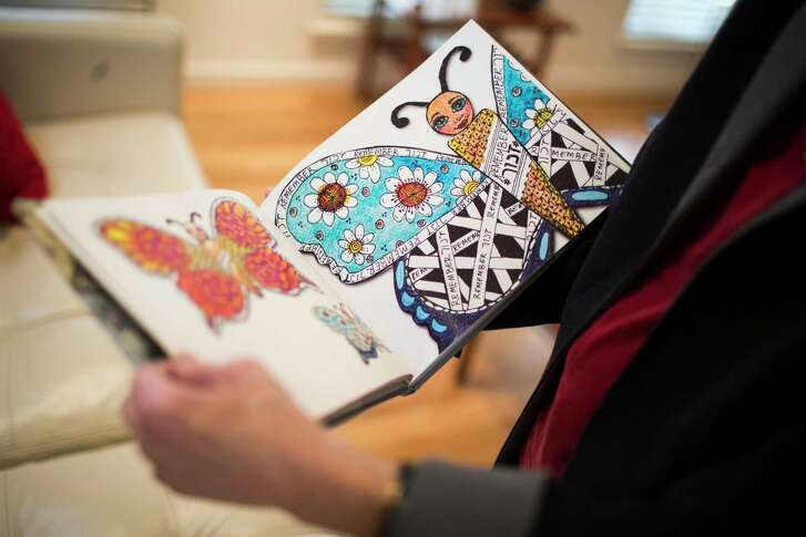 Chaja Verveer, a Holocaust survivor goes through the pages of the book titled, Taking Flight, which contains 100 pages showcasing the handcrafted butterflies from children and adults from all over the world honoring the 1.5 million children who perished during the Holocaust. Thursday, Jan. 25, 2018, in Houston.