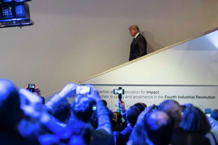 Participants at the World Economic Forum in Davos capture images of President Donald Trump on Thursday. A conciliatory Trump raised the possibility that he would re-enter a Pacific trade agreement he scrapped last year if it were renegotiated. Photo: Gian Ehrenzeller, SUB / © KEYSTONE / GIAN EHRENZELLER