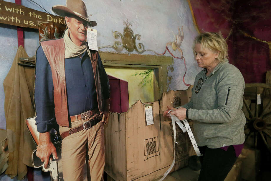 "Tammy Pullen, with The Nest Sale Services and Liquidation, puts price stickers on items including a model of the Alamo and a life-size cutout of John Wayne in the Cantina at Alamo Village near Brackettville on Thursday, Jan. 25, 2018.  There are approximately 2,400 items being liquidated this weekend from the movie set, where 72 motion pictures were filmed since the early 1950's, including ""The Alamo"" in 1959.  MARVIN PFEIFFER/mpfeiffer@express-news.net Photo: Marvin Pfeiffer, San Antonio Express-News / Express-News 2018"