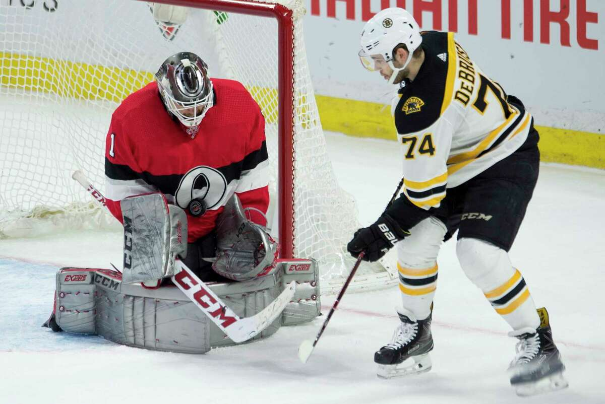 Boston Bruins left wing Jake DeBrusk (74) waits for a rebound as a shot hits Ottawa Senators goaltender Mike Condon (1) on the chest during the first period of an NHL hockey game Thursday, Jan. 25, 2018, in Ottawa, Ontario. (Adrian Wyld/The Canadian Press via AP)