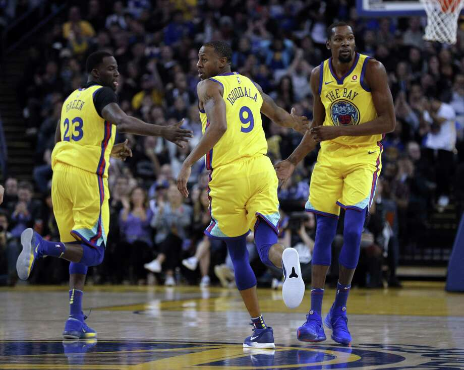 Andre Iguodala (9), Draymond Green (23) and Kevin Durant (35) high five in the first half as the Golden State Warriors played the Minnesota Timberwolves at Oracle Arena in Oakland, Calif., on Thursday, January 25, 2018. Photo: Carlos Avila Gonzalez / The Chronicle / ONLINE_YES