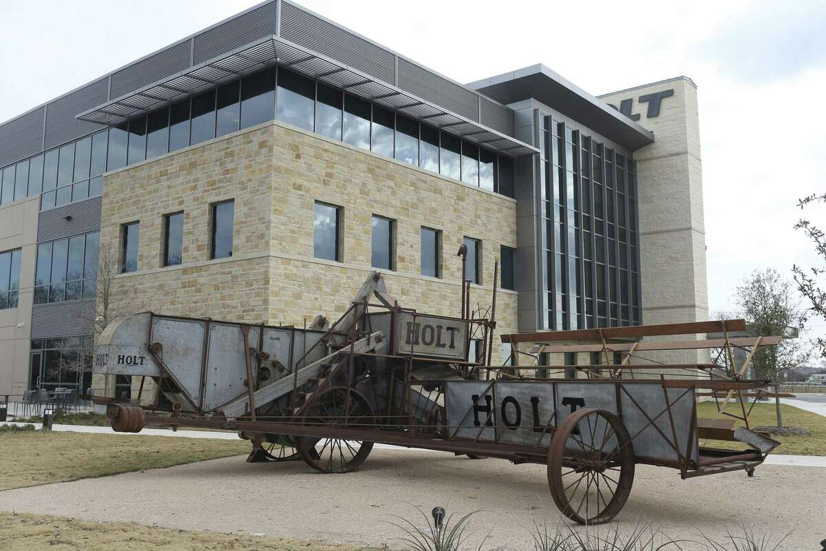 An antique harvester sits in front of Holt Cat's new headquarters building in San Antonio. The heavy equipment dealer saw an uptick in business starting in mid-2017.