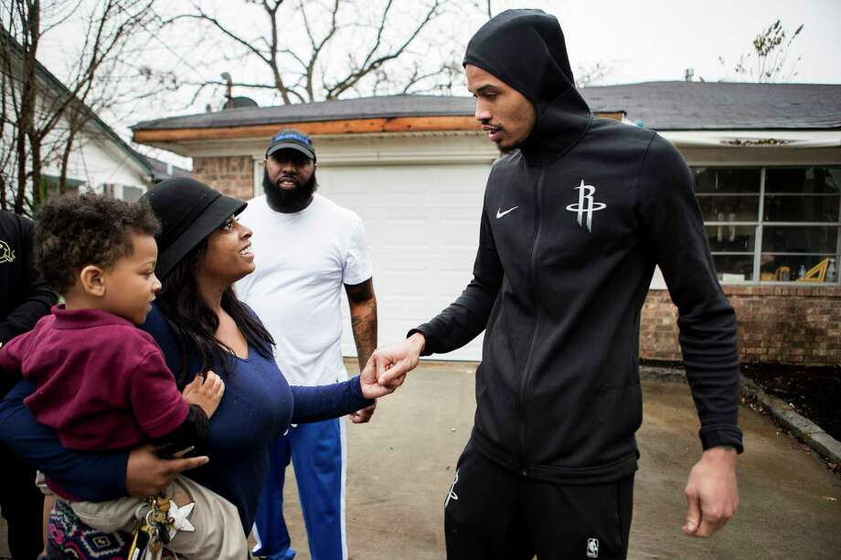 "Tia Joseph and her son, Corey Drouselle, greet Gerald Green outside her home. Green, Trae tha Truth and Justin ""DJ Mr. Rogers"" Rogers are helping rebuild the home. Photo: Brett Coomer, Staff / © 2018 Houston Chronicle"