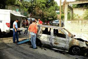 Forensic personnel and personnel of Guerrero state attorney's office work next to a car which was found with three calcined bodies inside in the outskirts of Acapulco, Guerrero state, Mexico, on January 25, 2018.  Nearly 19,000 people have been killed due to organized crime in Mexico in 2017, the most violent year in twenty years, according to a report revealed Tuesday by the Mexican NGO Semaforo Delictivo. Guerrero is one of Mexico's poorest and most violent states, where a lucrative drug trade has flourished. / AFP PHOTO / FRANCISCO ROBLESFRANCISCO ROBLES/AFP/Getty Images