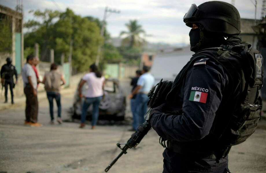 FILE - A police officer stands guard as personnel of Guerrero state attorney's office work next to a car which was found with three calcined bodies inside in the outskirts of Acapulco, Guerrero state, Mexico, on January 25, 2018.   On Wednesday, Feb. 7, 2018, five headless bodies were left in front of a