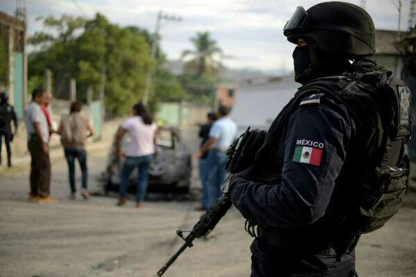 A police officer stands guard as personnel of Guerrero state attorney's office work next to a car which was found with three calcined bodies inside in the outskirts of Acapulco, Guerrero state, Mexico, on January 25, 2018. Nearly 19,000 people have been killed due to organized crime in Mexico in 2017, the most violent year in twenty years, according to a report revealed Tuesday by the Mexican NGO Semaforo Delictivo. Guerrero is one of Mexico's poorest and most violent states, where a lucrative drug trade has flourished. / AFP PHOTO / FRANCISCO ROBLESFRANCISCO ROBLES/AFP/Getty Images