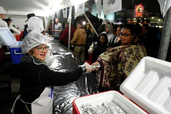 Yolanda Lopez hands out tacos during the annual Cowboy Breakfast to kick off the San Antonio Rodeo season at Cowboys Dance Hall on Friday morning, Jan. 26, 2018. Thousands of people received tacos, biscuits, milk and coffee.