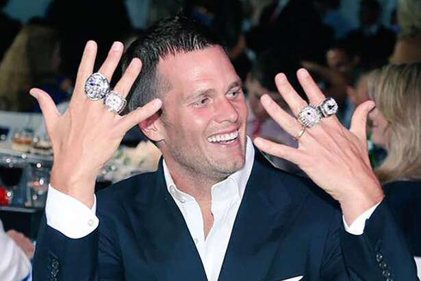New England Patriots quarterback Tom Brady shows off some of his Super Bowl rings at a team celebration.
