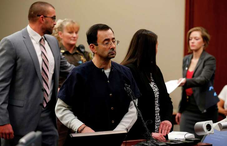 """Former Michigan State University and USA Gymnastics doctor Larry Nassar stands during the sentencing phase in Ingham County Circuit Court on January 24, 2018 in Lansing, Michigan. Disgraced former USA Gymnastics doctor Larry Nassar was sentenced to 40 to 175 years in prison on Wednesday for sexually abusing scores of young girls under the guise of medical treatment. """"I've just signed your death warrant,"""" Judge Rosemarie Aquilina said as she handed down the sentence after a week of gut-wrenching testimony by over 150 of Nassar's victims.  / AFP PHOTO / JEFF KOWALSKYJEFF KOWALSKY/AFP/Getty Images"""
