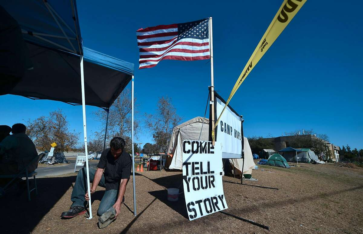 TOPSHOT - The US flag is hoisted at Camp Hope, a homeless encampment near the Honda Center in Anaheim, California on January 23, 2018. January 22 reports said authorities planned to clear out Orange County's largest homeless encampment with some 500 people living in tents. The Honda Center is home to the National Hockey League's Anaheim Ducks. / AFP PHOTO / FREDERIC J. BROWNFREDERIC J. BROWN/AFP/Getty Images
