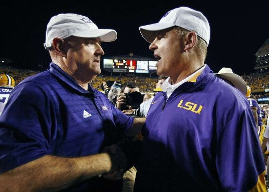 Northwestern State coach Bradley Dale Peveto, left, talks with LSU coach Les Miles after LSU's 49-3 win in an NCAA college football game in Baton Rouge, La., Saturday, Sept. 10, 2011. (AP Photo/Gerald Herbert) Photo: AP Photo/Gerald Herbert