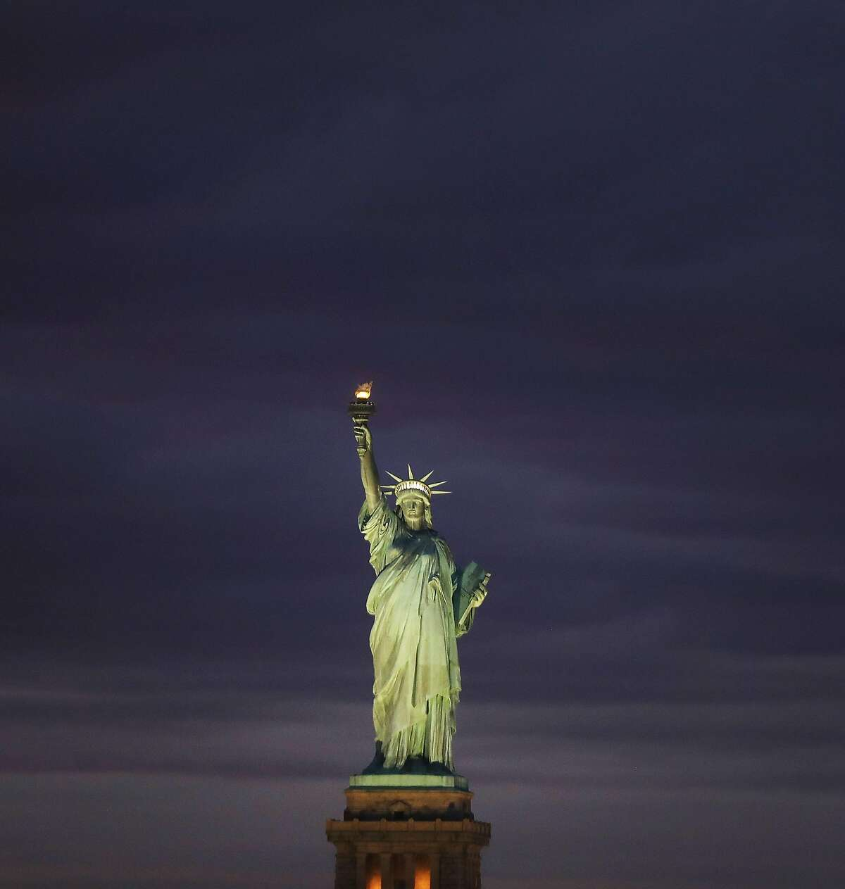 NEW YORK, NY - JANUARY 23: The Statue of Liberty stands in New York Harbor at sunset on January 23, 2018 in New York City. The national landmark only briefly closed due to the government shutdown which has temporarily been resolved. (Photo by Spencer Platt/Getty Images)