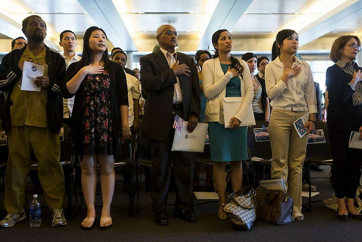 Fifty-five people stand during the National Anthem before swearing in as U.S. citizens during a naturalization ceremony put on by the Citizenship and Immigration Services, Seattle District 20, OneAmerica and the Seattle Office of Immigrant and Refugee Affairs on Friday, June 14, 2013, at Seattle City Hall in Seattle. The ceremony was part of a larger event celebrating Flag Day, which included local artists, face painting, crafts for kids and resources for new citizens. (Jordan Stead, seattlepi.com)