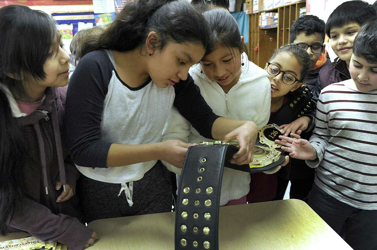 Students including from left, Kaylee Sanchez, Sheila Samaniego and Asli Castro, get a close look at the Super 32 National Championship Title belt won for wrestling by Danbury High School wrestler Jakob Camacho, 17, a senior at Danbury High School. Jakob spoke to forth-graders at Morris Street School in Danbury, Friday, January 26, 2018.