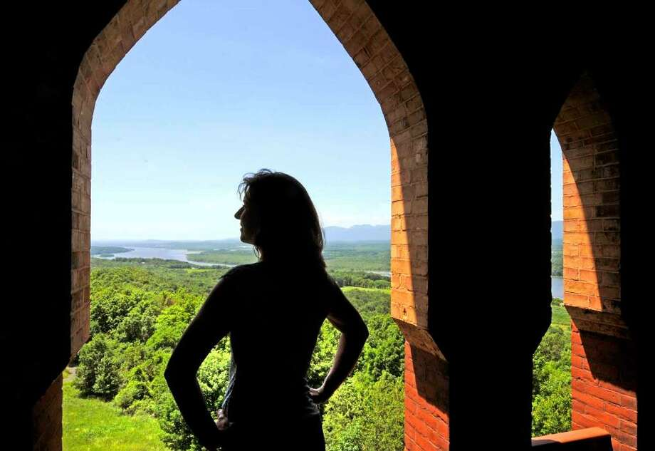 Olana curator Evelyn Trebilcock looks out over the Hudson River from the bell tower of the historic home of Hudson River School painter Frederic Edwin Church in Hudson. ( Michael P. Farrell / Times Union ) Photo: MICHAEL P. FARRELL