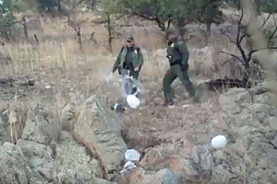 This Jan. 10, 2011, image from video provided by No More Deaths shows Border Patrol agents kicking over water bottles left for those crossing into the U.S. illegally in the Arizona desert. Photo: Uncredited, Associated Press