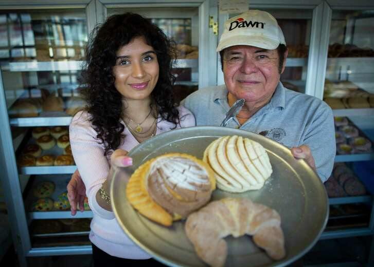 Jackie Garza, 18, and her father, Trinidad Garza, display some of the specialties at La Casa Bakery and Restaurant. Thousands of Twitter users who saw her message helped convince the elder Garza to keep the business open.