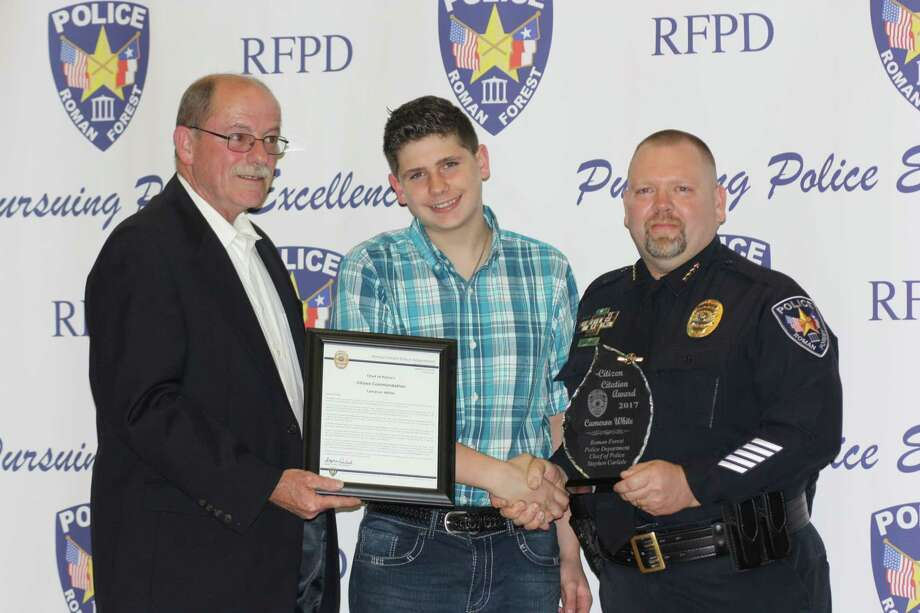 Two 12-year-old boys who saved the life of a drowning girl on Feb. 16, 2017, in Roman Forest were recognized with a Citizen Citation Award at the Roman Forest Police Officer Awards and Appreciation Dinner on Jan. 22 at the EMCID building in New Caney.  Pictured is Cameron White (center), his stepfather, Johnny Wolfe, and Roman Forest Police Chief Stephen Carlisle (right). Photo: Vanesa Brashier