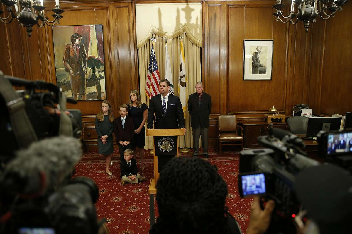 After being sworn in as interim mayor by City Attorney Dennis Herrera, Mark Farrell (center) with his wife, father and children address the members of the news media at City Hall, Tuesday, Jan. 23, 2018, in San Francisco, Calif.