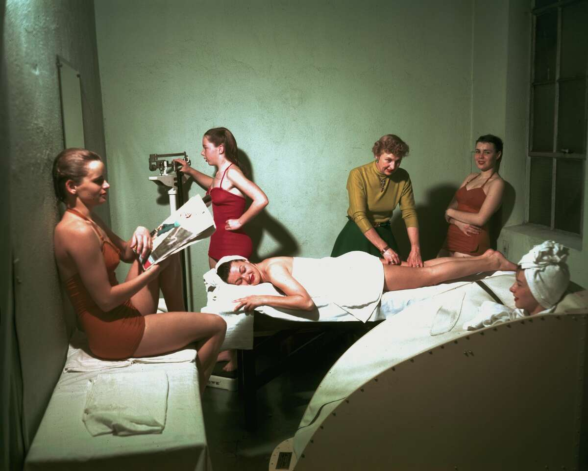 Members of Oakland's Athens Club synchronized swimming team relax after a practice in 1955. One receives a massage and another sits in a portable steam cabinet.