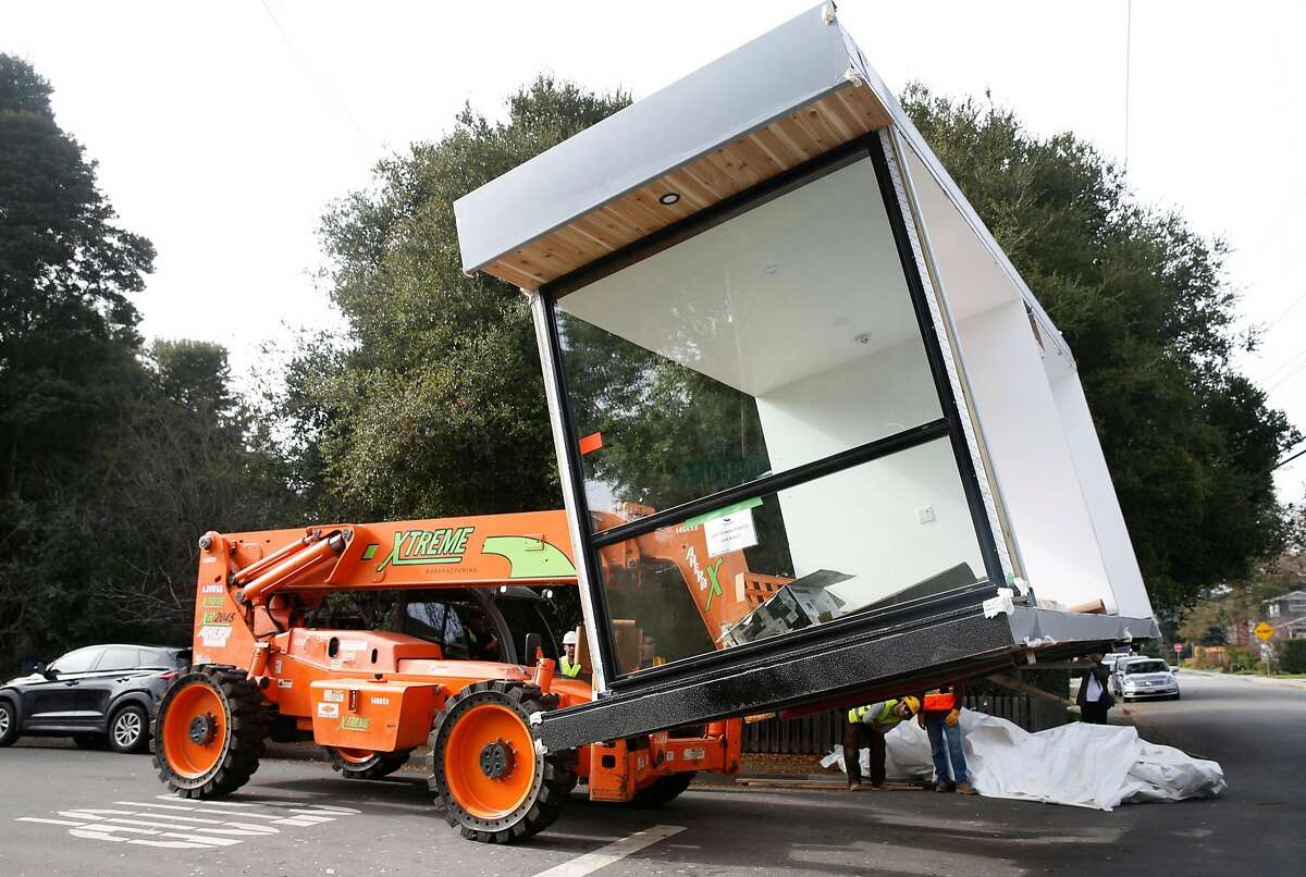 A section of a pre-fabricated home constructed using four shipping containers is lifted from a flatbed truck before installation in Joshua To's backyard in Menlo Park, Calif. on Friday, Jan. 12, 2018.