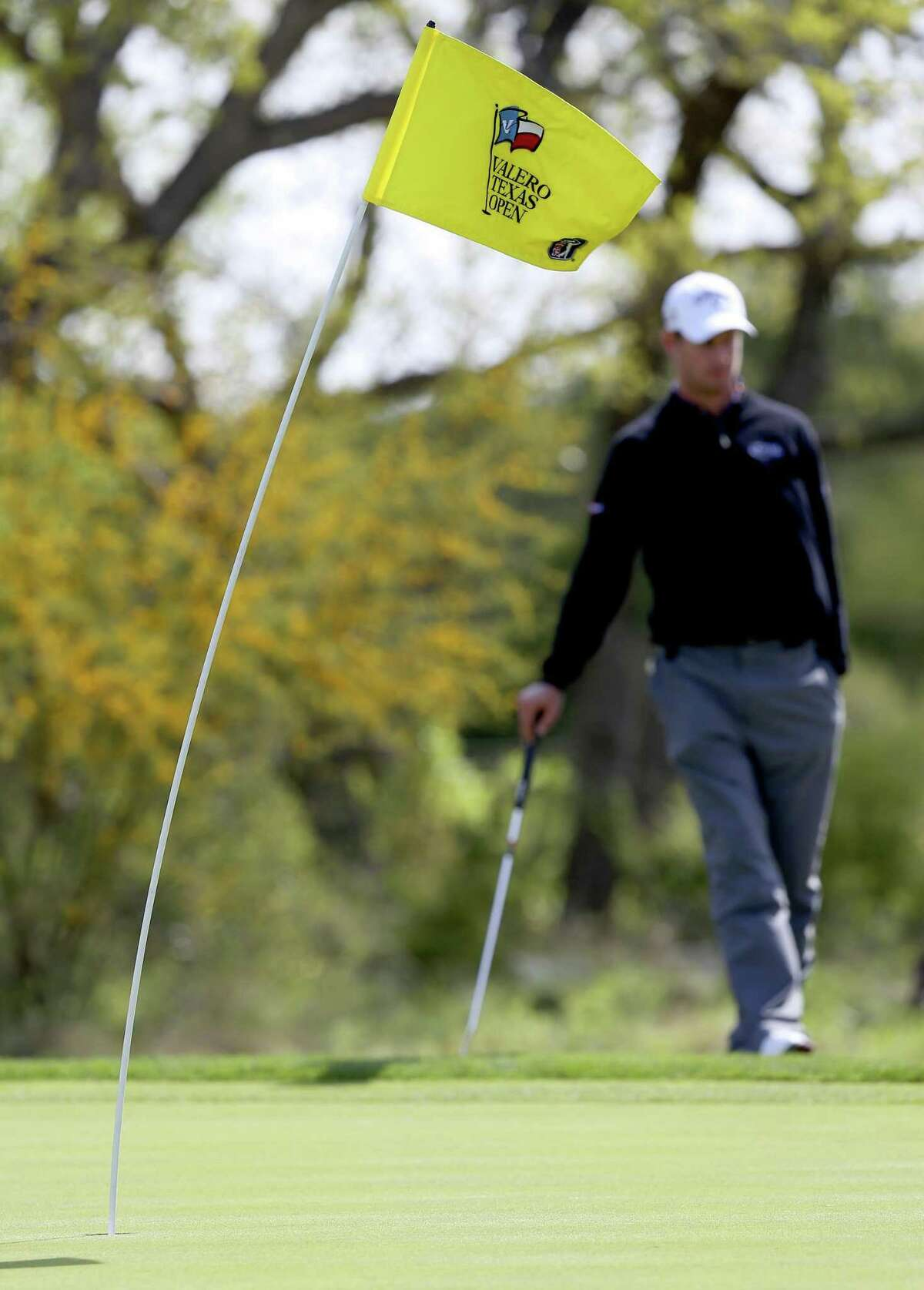 The first tee flag is blown to the side March 26, 2015 at the Texas Open by strong winds associated with a cold front during the first round of the tournament. The Open is contributing heavily to The First Tee.